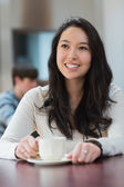 Smiling student sitting in a coffee shop — Stock Photo