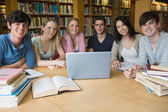 Six students learning in a library with a laptop — Stock Photo