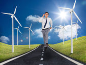 Businessman running on a road next to windmills — Stock Photo