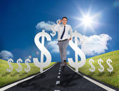 Businessman running on a road with dollar signs — Stock Photo