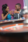 Couple sitting clinking glasses at the roulette table — Stock Photo