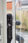 Burglar opening the terrace door — Stock Photo