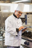 Smiling chef using digital tablet — Stock Photo