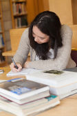 Student sitting in a library at a desk and writing — Stock Photo