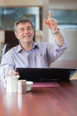 Man in a coffee shop calling the waiter — Stock Photo