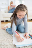 Little girl drawing sitting on floor with mother reading newspaper — Stock Photo