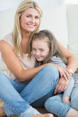 Mother and daughter hugging in living room — Stock Photo