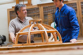 Teacher and student talking about a wooden frame — Stock Photo