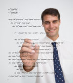 Smiling businessman writing in sql language — Stock Photo
