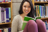 Student in a library sitting on the floor — Stock Photo