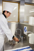 Concentrated chef washing hands — Stock Photo
