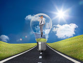 Businessman in light bulb with wind turbines and solar panels — Stock Photo