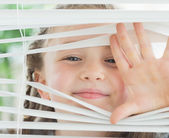 Smiling girl looking through the blinds — Stock Photo