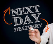 Woman writing next day delivery with a chalk — Stock Photo