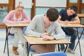 Writing students at desks in a classroom — Stock Photo