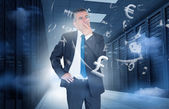 Businessman standing in data center with currency graphics — Stock Photo