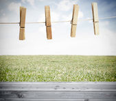 Clothespin on a laundry line outside above wooden boards — Stock Photo