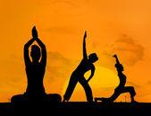 Silhouette of women doing yoga — Stock Photo