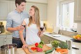 Couple enjoying drinking wine and cooking — Stock Photo