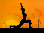 Silhouette of woman doing yoga with wind turbines — Stock Photo
