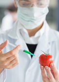 Woman injecting a tomato — Stock Photo