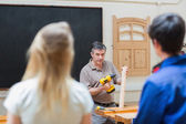 Teacher of a woodwork class teaching two students — Stock Photo