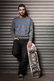 Attractive skater leaning against metal shutters — Stock Photo