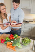 Couple reading cookery book — Stockfoto