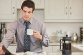 Man drinking coffee and reading newspaper — Stock Photo