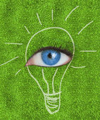 Blue eye surrounded by a drawing of a light bulb — Stock Photo