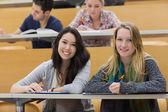 Mädchen lächelnd im hörsaal mit tabletpc — Stockfoto