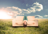 Woman sitting upside down on couch in field — Stock Photo