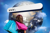 Girl with shopping bags looking at address bar with large earth — Stock Photo