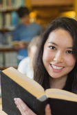Student in library reading book — Stock Photo