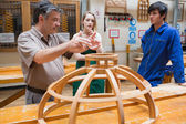 Two students and an explaining teacher in a woodwork class — Stock Photo