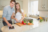 Man pointing on tablet pc with woman chopping peppers — Stock Photo