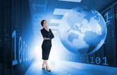 Businesswoman standing in data center with earth and binary code graphics — Stock Photo