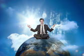Businessman sitting on top of the world — Stock Photo