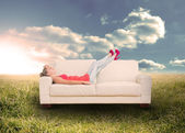 Woman relaxing on couch in field — Stock Photo