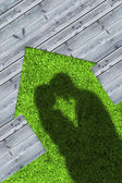 Shadows of embracing couple on wooden boards representing a house — Stock Photo