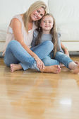 Mother and daughter sitting on the floor embracing — Stock Photo