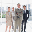 Boss standing with his arms folded with serious colleagues behind — Stock Photo
