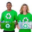 Stock Photo: Two cheerful environmental activists holding box of recyclables