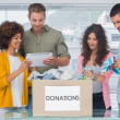 Volunteers using tablet and taking out clothes from a donation box — Stock Photo