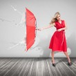 Attractive woman holding an umbrella to protect herself from the — Stock Photo #26979041