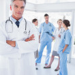 Doctor with arms folded in front of his medical team — Stock Photo #26979669