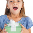 Excited little girl holding a wrapped gift — Stock Photo