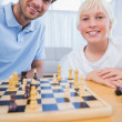 Stock Photo: Father playing chess with his little boy