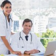 Cheerful doctors posing together in their office — Stock Photo #26979903
