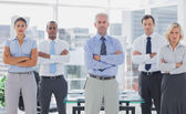 Team of business standing with arms folded — Stock Photo